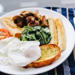 Plato con huevo, salchichas, tomate, espinacas y pan