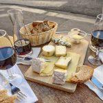 Variedad de quesos acompañados de dos copas de vino